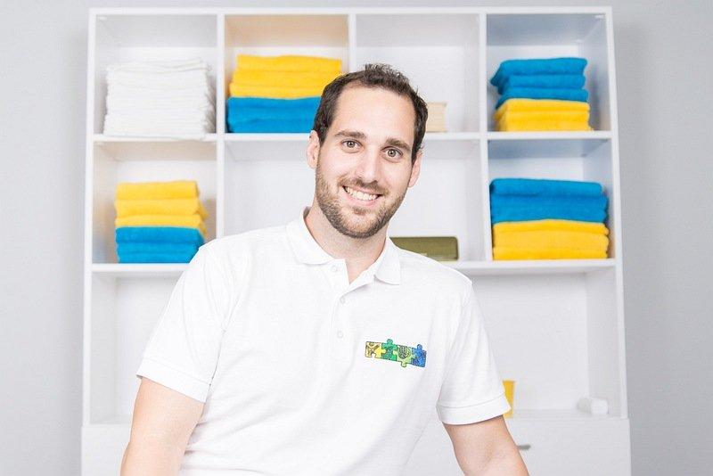 Über mich als Therapeut. Ich stehe im Therapieraum und warte auf Kundinnen und Kunden. Kuschelige, schöne und bunte Handtücher sind bereit zur Verwendung.